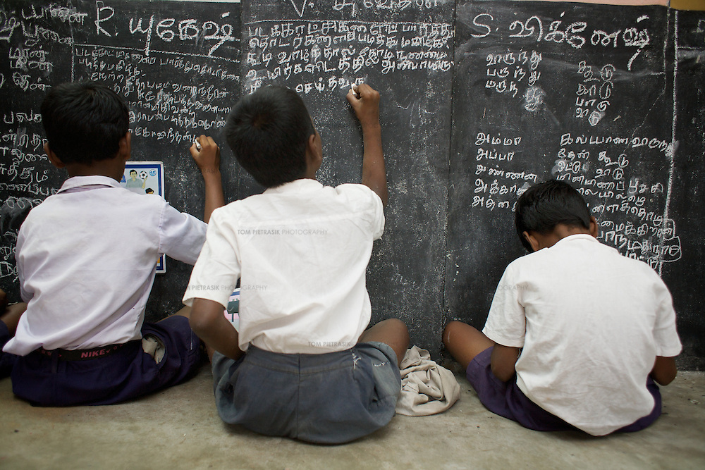 Pupils write at at the low-level blackboard that is a feature of all ABL classrooms. ..At Periyakuppam village primary school, in tsunami-affected Cuddalore district, all 1-4 Grade students (87 pupils) are completing the ABL curriculum. Almost all of these students are  tsunami-affected and from poor fishing families. With the assistance of Unicef and the Tamil Nadu Government, the school has been pursuing ABL since 2005 and is one of the model schools for the government's wider implementation of the program. Unicef has supplied the school teaching advice, tables, and learning equipment including the activity cards that are the basis of ABL learning. ..ABL (Activivity Based Learning) was first implemented in Chennai City government schools. Such was the success of the program that Unicef developed the model and worked with the Tamil Nadu government to introduce it to all 330 schools in the three tsunami affected districts of Cuddalore, Nagappatinam and Kanyakumari. On the basis of the tsunami-schools' experience, the Government of Tamil Nadu has now applied the scheme for all 1-5 Grade students in all government schools in the state. ABL encourages children to learn at their own pace, individually or in small groups. It dispenses with the idea of the class teacher standing at the blackboard with all pupils looking forward. Children are inspired to consider learning a creative and enjoyable experience. Using a series of task-cards, students are taught to take responsibility for their own achievements and to pursue their studies at a steady pace. The class teacher is on hand for any assistance required by pupils. Unicef has provided learning materials, tables and advice to the Tamil Nadu government. Other Indian state education administrations are now looking to Tamil Nadu with the idea that they might themselves implement ABL...Cuddalore, Tamil Nadu, India.December 8th 2008..THIS PHOTOGRAPH IS THE COPYRIGHT OF TOM PIETRASIK. THE PHOTOGRAPH MAY NOT BE REPRODUCED IN AN
