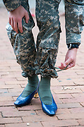 An ROTC student ties up his uniform pants to show off his heels for the Womens Centers sixth annual Walk a Mile in Her Shoes event.  Photo by Elizabeth Held