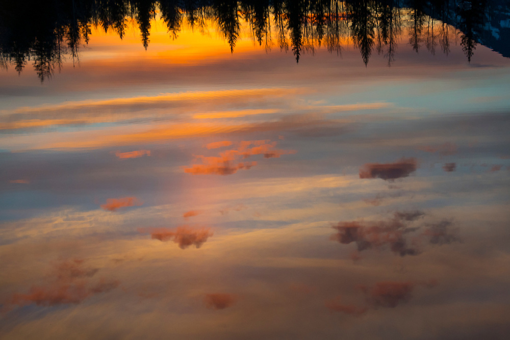 A vivid colored sunset reflects brilliant orange and blue clouds in a pond surrounded by spruce trees in Alaska.