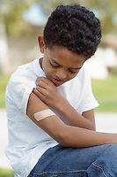 Boy (7-9) examining bandaid on arm, outdoors