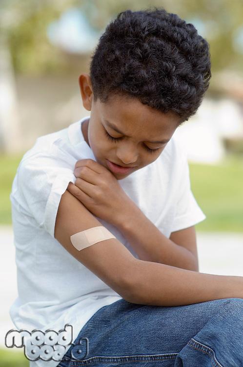 Boy (7-9) examining bandaid on arm, outdoors