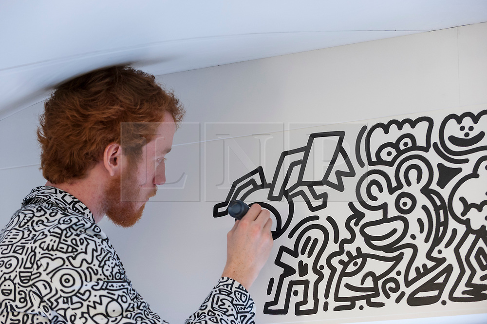 """© Licensed to London News Pictures. 07/04/2018. LONDON, UK. The artist Mr Doodle creates his distinctive artwork in The Doodle Room at """"Sense of Space"""", an art pop-up which has opened to the public in Broadgate.  Comprising four rooms to challenge the visitor's sensory perceptions through art, the installation is open until 18 May.  Photo credit: Stephen Chung/LNP"""