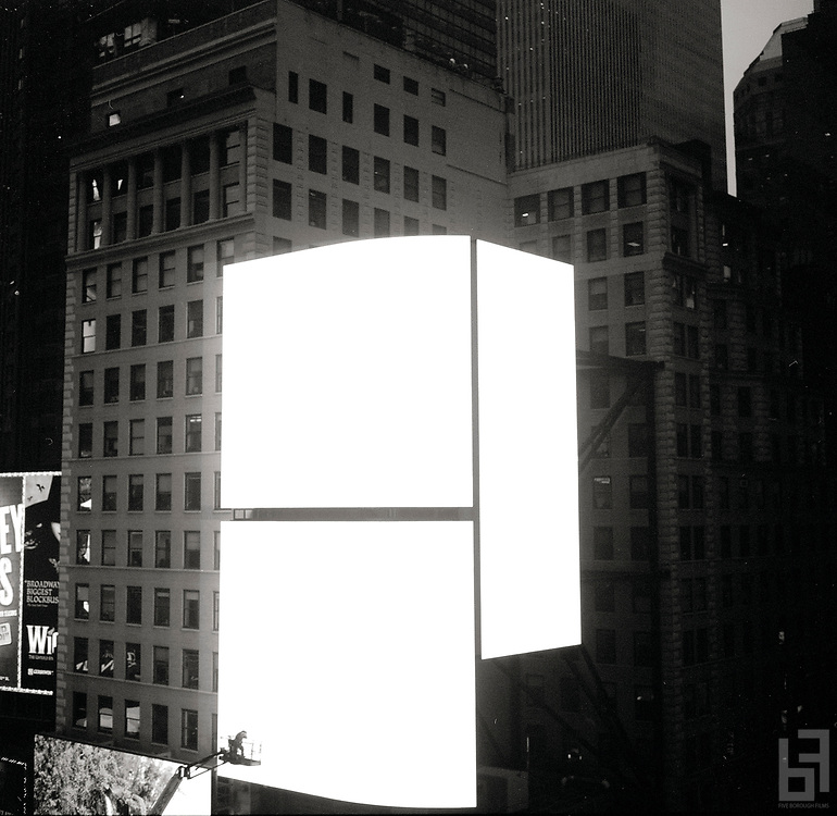 """worker in a crane basket inspects a new super large LED panel in Times Square above the I.Miller Building  Taken from the series """"Down with the Ship"""""""