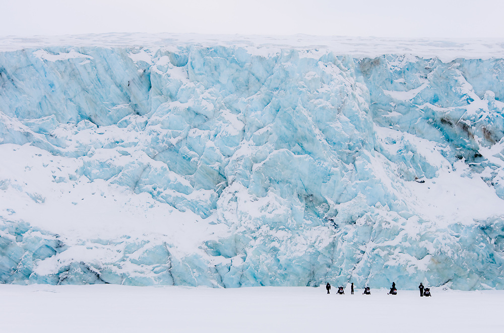 People admiring the power and grace of a glacier front of Paulabreen on Svalbard.