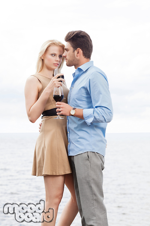 Romantic young couple having red wine against sea