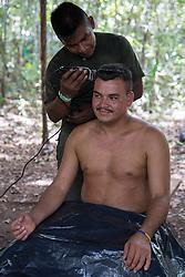 El Diamante, Meta, Colombia - 18.09.2016        <br /> <br /> A FARC fighter getting a hair cut in a guerilla camp during the 10th conference of the marxist FARC-EP in El Diamante, a Guerilla controlled area in the Colombian district Meta. Few days ahead of the peace contract passing after 52 years of war with the Colombian Governement wants the FARC decide on the 7-days long conferce their transformation into a unarmed political organization. <br /> <br /> Ein FARC Kaempfer bekommt seine Haare geschnitten im Guerilla-Camp, am Rande der zehnten Konferenz der marxistischen FARC-EP in El Diamante, einem von der Guerilla kontrollierten Gebiet in der kolumbianischen Region Meta. Wenige Tage vor der geplanten Verabschiedung eines Friedensvertrags nach 52 Jahren Krieg mit der kolumbianischen Regierung will die FARC auf ihrer sieben taegigen Konferenz die Umwandlung in eine unbewaffneten politischen Organisation beschlieflen. <br />  <br /> Photo: Bjoern Kietzmann