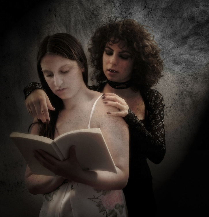 Two young women together reading a book
