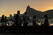 Residents gather to watch the sunset over Christ the Redeemer statue along Guanabara Bay at the Urca neighborhood in Rio de Janeiro, Brazil.