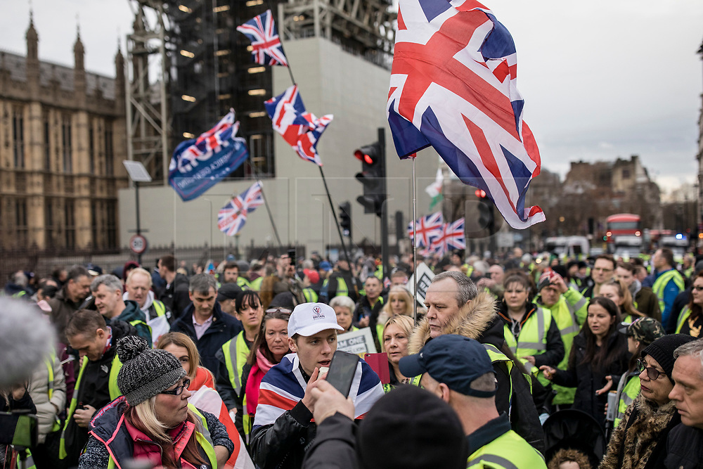 """© Licensed to London News Pictures. 12/01/2019. London, UK. Pro-Brexit """"yellow vest"""" protesters block Westminster Bridge in London. James Goddard, who was involved in an incident with Conservative MP Anna Soubry, was arrested by police this morning. Photo credit: Rob Pinney/LNP"""