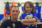 AFC Wimbledon Defender and Captain Barry Fuller (2) with the mascot before the Pre-Season Friendly match between AFC Wimbledon and Watford at the Cherry Red Records Stadium, Kingston, England on 15 July 2017. Photo by Jon Bromley.