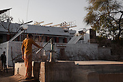A young girl taking drinking water, just outside from Barefoot College new campus; on the roof, some men are installing new solar panels. In 1972 Barefoot College started by the main problem of rajasthanies villages: drinking water access. 01/2013 © Marida Augusto/Max HIrzel