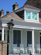House with rocking chairs on the porch in the French Quarter in New Orleans, Louisiana. Historic street light still damaged from Hurricane Katrina!