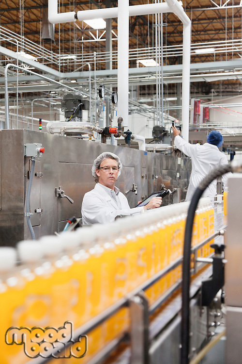 Factory men working in a bottling plant