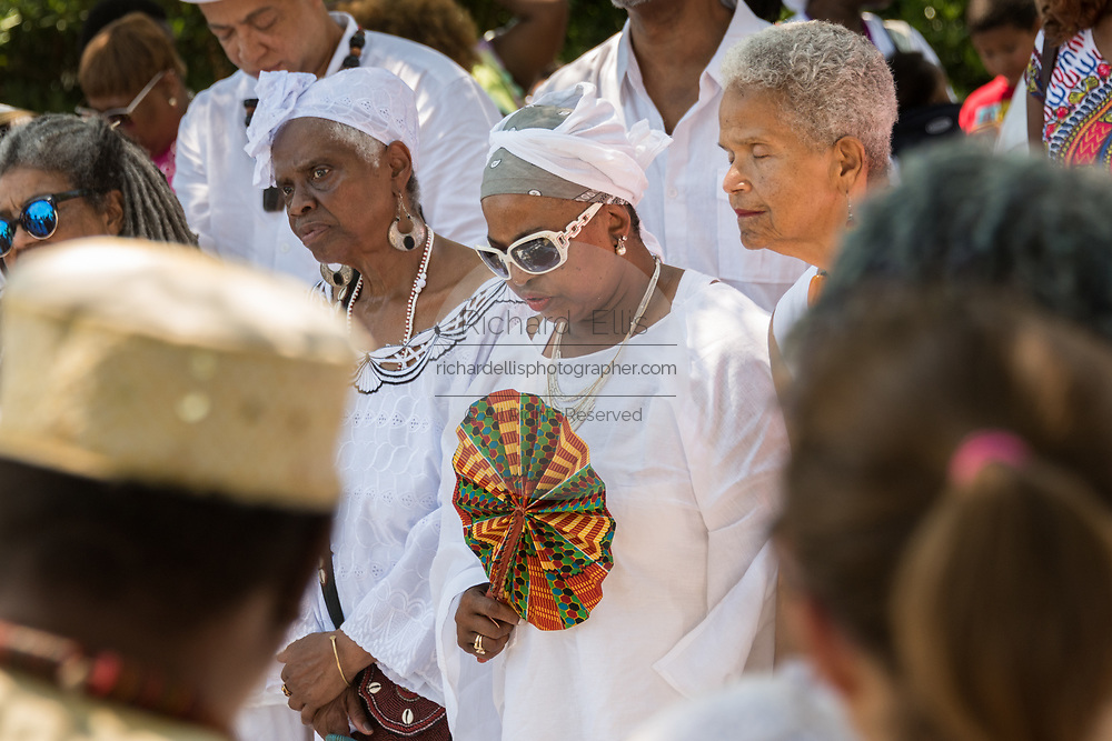 Descendants of enslaved Africans brought to Charleston in the Middle Passage hold a prayer service during a remembrance ceremony at Fort Moutrie National Monument June 10, 2017 in Sullivan's Island, South Carolina. The Middle Passage refers to the triangular trade in which millions of Africans were shipped to the New World as part of the Atlantic slave trade. An estimated 15% of the Africans died at sea and considerably more in the process of capturing and transporting. The total number of African deaths directly attributable to the Middle Passage voyage is estimated at up to two million African deaths.