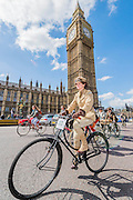 "Passing the Houses of Parliament, Westminster. The Tweed Run 2015 - it's 7th annual British public bicycle ride through London's historic streets, with a prerequisite that participants are dressed in their best tweed cycling attire. There are also plenty of handle bar moustaches, penny farthings and Union Jacks. ""Guests can expect a leisurely day cycling, stopping at some of London's most iconic landmarks to enjoy a spot of tea, a picnic in the park and finally a jolly good knees-up in a beautiful art-deco ballroom for the Tweed Run closing ceremony. Starting at Trafalgar Square, the cyclists then embarked on a 12 mile scenic ride through London, stopping at traditional spots."