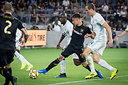 LAFC forward Brian Rodriguez (20) tries to move the ball past Minnesota United defenders Brent Kallman (14) and Minnesota United midfielder Lawrence Olum (12) during an MLS soccer match against the Minnesota United. Minnesota United defeated the LAFC 2-0 on Sunday Sept. 1 2019, in Los Angeles. (Ed Ruvalcaba/Image of Sport)