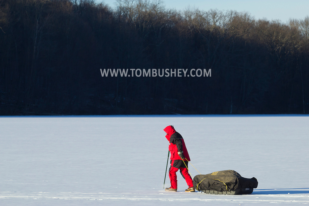 Montgomery, New York - A man pulls his ice fishing equipment across Diamond Lake in Winding Hills Park on Saturday, Jan. 24, 2014.