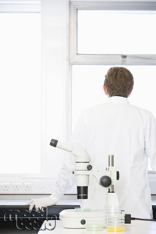 Scientist standing behind microscope in laboratory