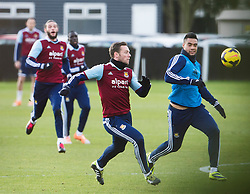 © London News Pictures. 28/01/2014. London, UK. Striker ANDY CARROLL (left) and team captain KEVIN NOLAN (centre) during West Ham United training at their training ground in Chadwell Heath, East London ahead of their premiership game away to Chelsea on tomorrow night (29/01/2014). Photo credit: Ben Cawthra/LNP