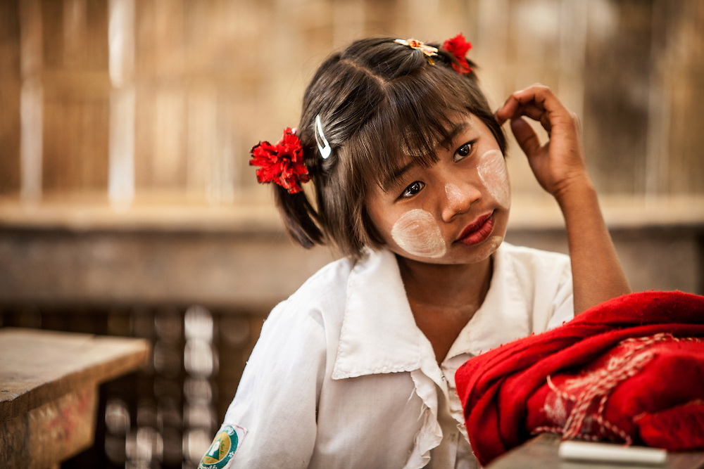 A young girl in a Chin village school cogitates in the classroom during down time. There are a group of river-side villages with Chin people located near Mrauk U in the Rakhine State of Myanmar.