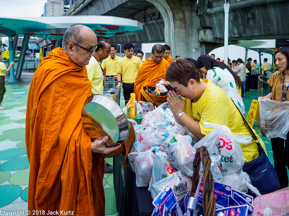 26 JULY 2018 - BANGKOK, THAILAND: A woman prays after making a donation to a monk during a merit making ceremony in the Pathumwan area of Bangkok to honor Thai King His Majesty King Maha Vajiralongkorn Bodindradebayavarangkun, also known as Rama X, for his 66th birthday. The King's birthday is 28 July, and events are scheduled throughout Thailand to honor His Majesty. The Pathumwan merit making was organized by businesses in the area.     PHOTO BY JACK KURTZ