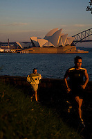 The Sydney Skyline featuring the Opera House and the Harbour Bridge in the background as early morning runners travel around the landmark Mrs Macquaries Chair in the Sydney Botanical gardens.
