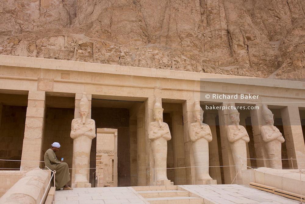 """Portrait of a local guide near the colossi of Pharaohs at the ancient Egyptian Temple of Hatshepsut near the Valley of the Kings, Luxor, Nile Valley, Egypt. The Mortuary Temple of Queen Hatshepsut, the Djeser-Djeseru, is located beneath cliffs at Deir el Bahari (""""the Northern Monastery""""). The mortuary temple is dedicated to the sun god Amon-Ra and is considered one of the """"incomparable monuments of ancient Egypt."""" The temple was the site of the massacre of 62 people, mostly tourists, by Islamists on 17 November 1997."""