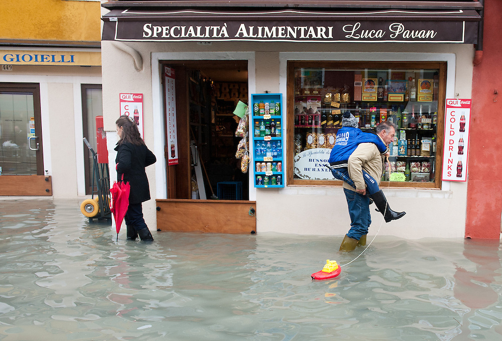 A man carries his son of the shoulder while he pulls a plastic boat in flooded Burano More than 59% of Venice was under water on Thursday, as the historic lagoon town was hit by exceptionally high tides. The sea level rose above 140cm overnight and was expected to remain above critical levels for about 15 hours.