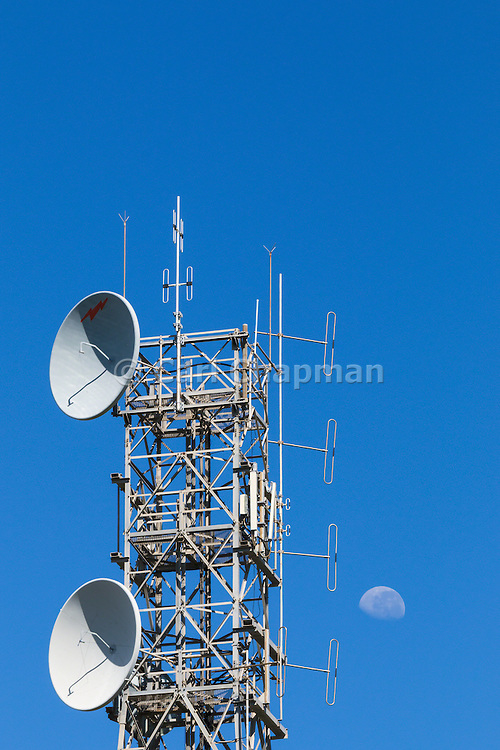 microwave and mobile radio antennas on tower with moon in background on Mt Stuart, Townsville, Queensland, Australia
