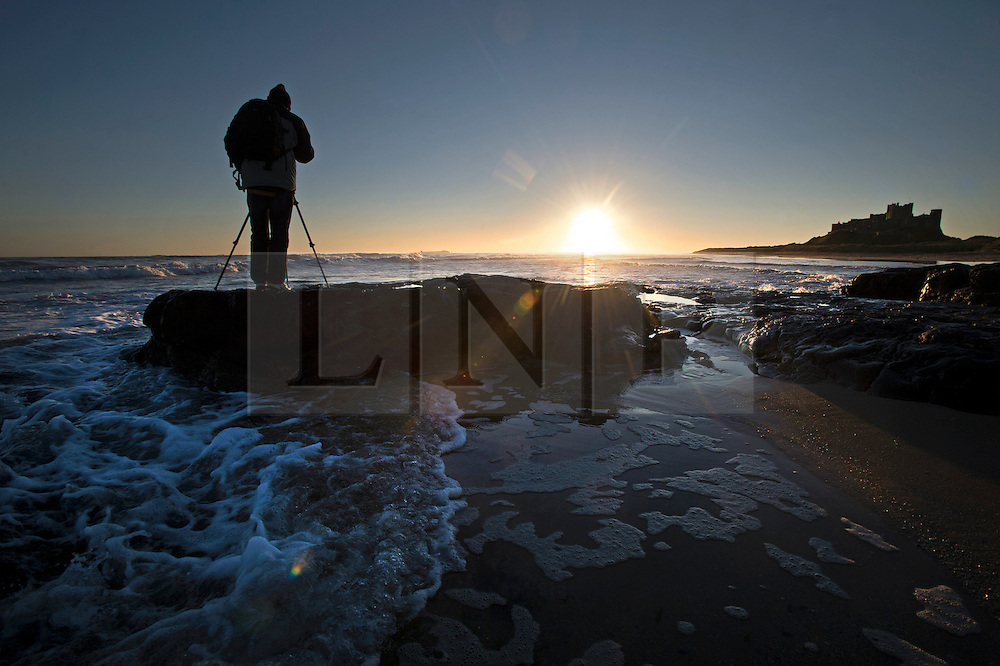 © Licensed to London News Pictures. 07/10/2012. Bamburgh, UK.  A photographer taking pictures from on top of a rock  at sunrise on Bamburgh beach in front of BAmburgh Castle (right) in Northumberland, UK on October 7, 2012. Photo credit : Ben Cawthra/LNP