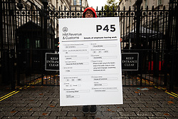 © Licensed to London News Pictures. 24/09/2019. London, UK. A demonstrator stands outside the gates to Downing Street with a large P45 form on a placard, following a historic ruling by the Supreme Court this morning that Boris Johnson's decision to suspend Parliament for five weeks was unlawful. Photo credit : Tom Nicholson/LNP