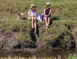 © Licensed to London News Pictures. 25/06/2020. London, UK. Sarah Clarke 35 from Putney and Sophie Lewis 32 from Richmond cool off along the banks of the Beverley Brook in Richmond Park in South West London as forecasters predict the hottest day of the year with temperatures expected to reach 33c. Prime Minister, Boris Johnson announces this week that tourism and hospitality, including pubs, restaurants and campsites can now reopen from the 4th of July as well as reducing the 2 metre rule to 1 metre. Photo credit: Alex Lentati/LNP