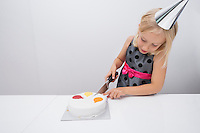 Girl cutting birthday cake at table in house