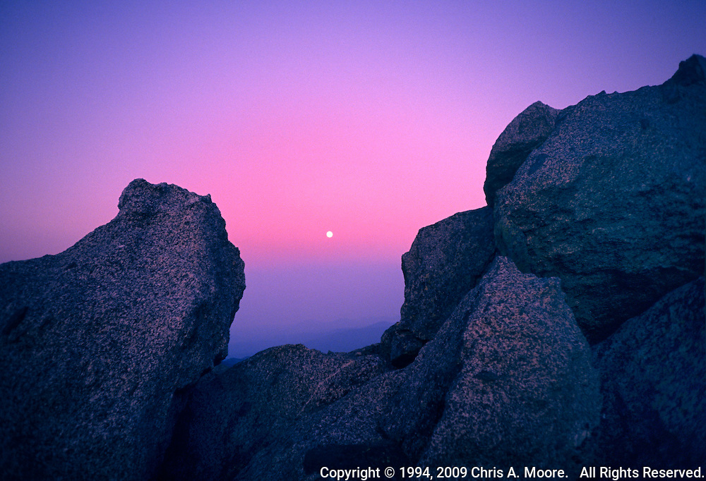 The moon rises between granite boulders at sunset on Mount Goliath, Colorado. August 1994
