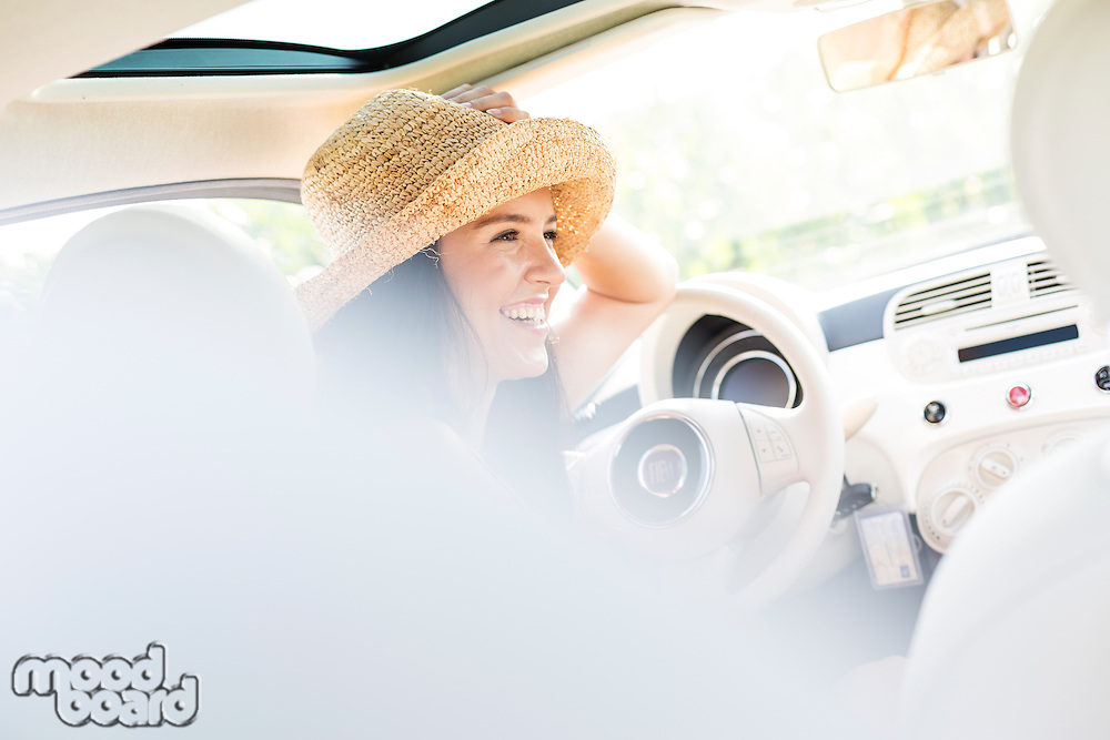 Happy woman sitting in car
