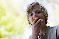 Portrait of boy (10-12) eating apple
