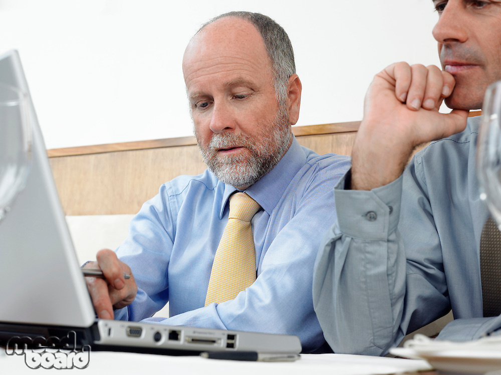 Businessmen using laptop indoors
