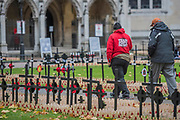 A team poppy factory member helps veterans locate their units section - Volunteers from the Royal British Legion set out the Field of Remembrance outside Westminster Abbey. The field comprises thousands of poppies on crosses to remember individuals and units. It will be completed in time for a Royal visit on Thursday . London 07 Nov 2017.