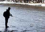 A man fishes in the Neversink River in Cuddebackville, New York, on the opening day of trout season in New York State. Most of the riverbank is still covered in snow and ice.