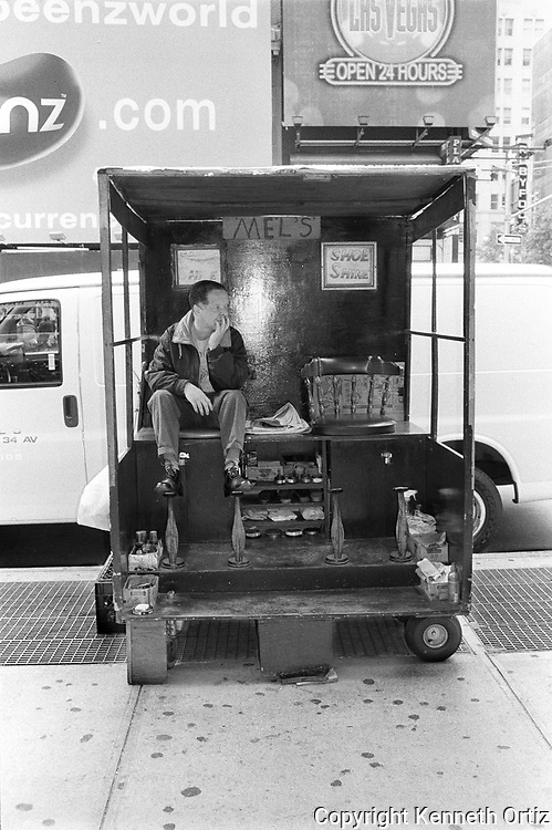 A shoe shiner sitting inside his shoe shine station on 7th Avenue in Manhattan.