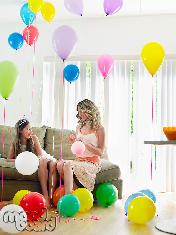 Girl (10-12) with mother sitting on sofa in room full of balloons