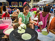 25 JUNE 2016 - BANGKOK, THAILAND:  A woman makes Thai deserts of roti flatbread in the platform area of Hua Lamphong train station during the station's centenary celebration. Hua Lamphong opened on June 25, 1916 after six years' construction. The station was built in an Italian Neo-Renaissance-style, with decorated wooden roofs and stained glass windows. The architecture is attributed to Turin-born Mario Tamagno. There are 14 platforms, 26 ticket booths, and two electric display boards. Hua Lamphong serves over 130 trains and approximately 60,000 passengers each day. Since 2004 the station has been connected by an underground passage to the MRT (Metropolitan Rapid Transit) subway system's Hua Lamphong Station.     PHOTO BY JACK KURTZ