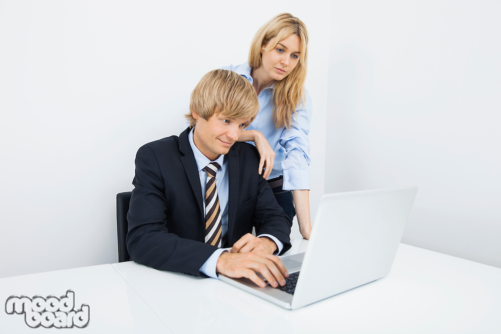 Businesspeople working on laptop at desk in office