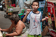"Mar. 21, 2009 -- BANGKOK, THAILAND: A boy blows bubbles in an alley in the Monk's Bowl Village. The Monk's Bowl Village on Soi Ban Baat in Bangkok is the only surviving one of what were originally three artisan's communities established by Thai King Rama I for the purpose of handcrafting ""baat"" the ceremonial bowls used by monks as they collect their morning alms. Most monks now use cheaper factory made bowls and the old tradition is dying out. Only six or seven families on Soi Ban Baat still make the bowls by hand. Most of the bowls are now sold to tourists who find their way to hidden alleys in old Bangkok. The small family workshops are only a part of the ""Monk's Bowl Village."" It is also a thriving residential community of narrow alleyways and sidewalks.     Photo by Jack Kurtz"