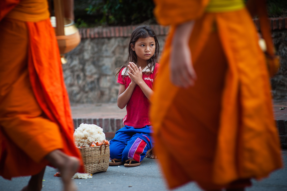 Girl giving alms to Buddhist monks at dawn in Luang Prabang (Laos).