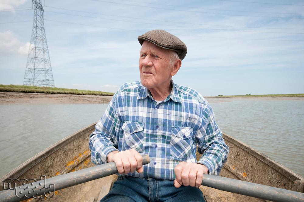 Elderly man rowing a boat on a reservoir