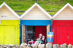 © Licensed to London News Pictures. 24/05/2016. Scarborough UK. A lady enjoys today's sunshine at her beach hut on Scarborough Beach in Yorkshire. Photo credit: Andrew McCaren/LNP