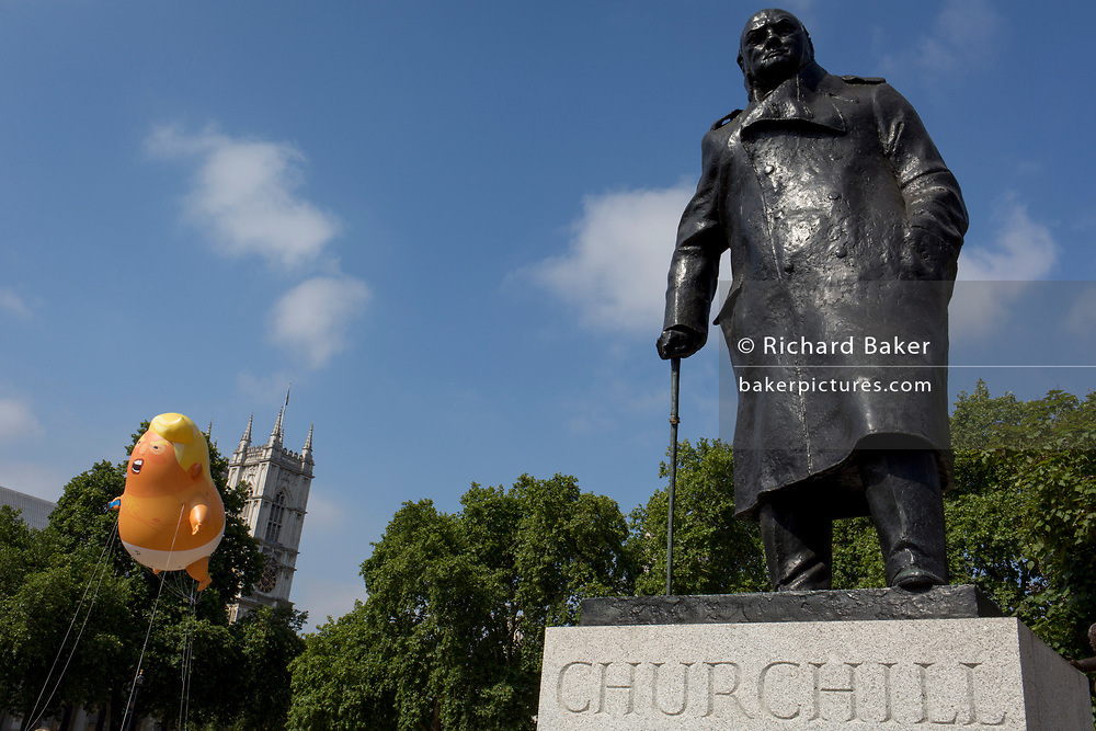 The inflatable balloon called Baby Trump flies above the statue of wartime Brish Prime Minister Winston Churchill in Parliament Square, Westminster, the seat of the UK Parliament, during the US President's visit to the UK, on 13th July 2018, in London, England. Baby Trump is a 20ft high orange blimp depicting the US President as an enraged, smartphone-clutching infant - and given special permission to appear above the capital by London Mayor Sadiq Khan because of its protest rather than artistic nature. It is the brainchild of Graphic designer Matt Bonner. (Photo by Richard Baker / In Pictures via Getty Images)