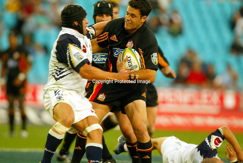 10 April, 2004. Rugby Union Super 12. Ellis Park Stadium, Johannesburg, South Africa. Cats vs Chiefs. David Hill runs into the tackle from Roland Bernard. The Cats defeated the Chiefs 23-21.<br /> Pic: Photosport