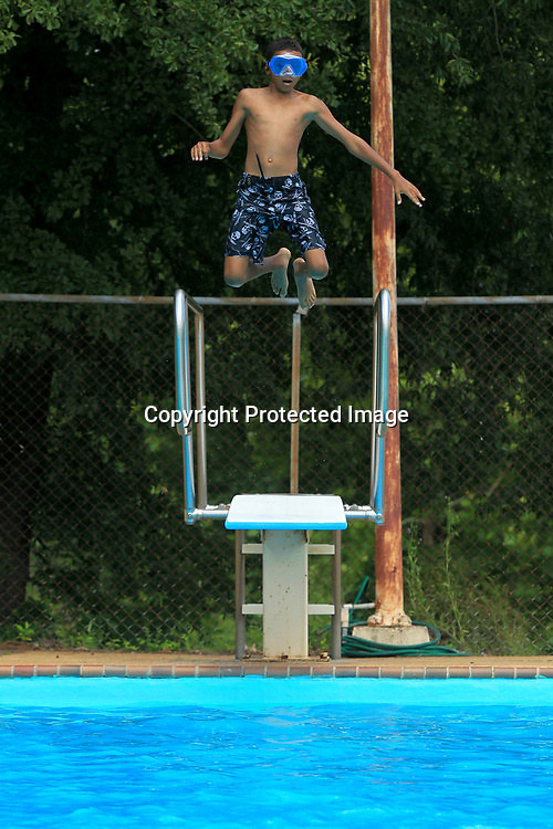 Jakobi Echoles, 11, of Tupelo, soars in the air as he jumps off the diving board as swims with his brothers and sisters at C.C. Augustus Pool in Tupelo Wednesday afternoon.
